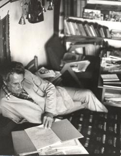 1974. Dolgozószobájában, csonka kezén támaszkodva, ahogyan írni szokott. Háttérben csengőgyűjteményének egy része. (Szokolai István felvétele a Könyvtáros folyóirat – 1986/11. 685. p. – részére.)